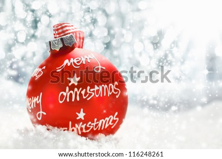 Beautiful atmospheric Merry Christmas greeting card with a red decorated bauble bearing the words Merry Christmas on a bed of snow with the sun bouncing off falling snowflakes with copyspace - stock photo