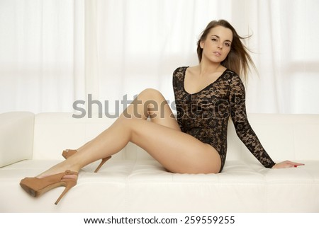 Beautiful attractive and sexy young adult sensuality pretty brunette woman wearing black lingerie on the white couch in luxury style apartment - stock photo