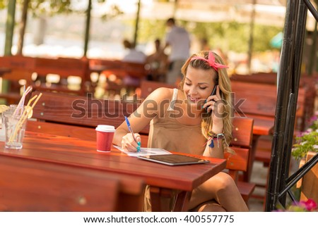 Beautiful attractive blond girl sitting in an outdoor cafe, having a phone conversation and writing notes - stock photo