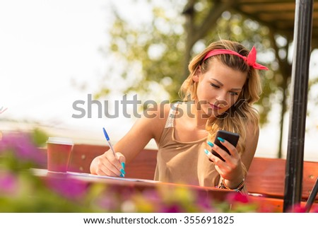 Beautiful attractive blond girl sitting in an outdoor cafe, holding a mobile phone and writing notes - stock photo