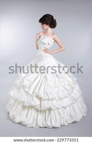 Beautiful attractive bride model wearing in wedding dress with voluminous skirt, studio photo - stock photo