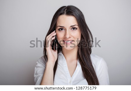 Beautiful attractive casual young woman talking on her mobile phone. Studio shot over gray background. - stock photo