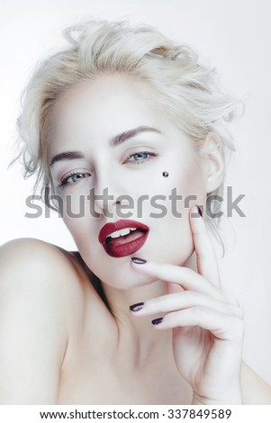 Beautiful attractive charming caucasian woman with perfect white skin and red lips posing in studio white background.