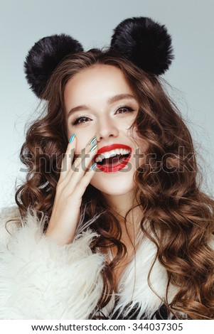 Beautiful attractive charming young caucasian girl with brown chocolate shiny hair posing with black ears on her head. - stock photo