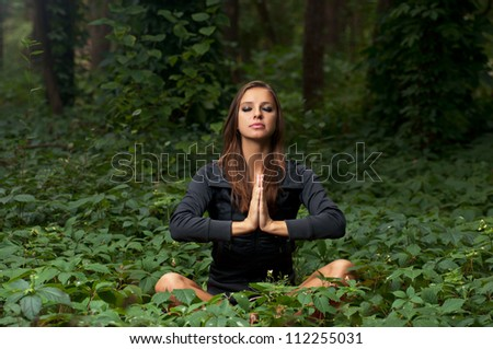 Beautiful attractive girl meditating outdoors in lotus pose