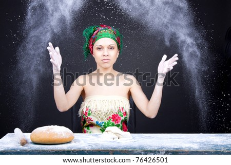 beautiful attractive girl sitting at the table and mix dough, kneading pizza ( bread ), cook concept. - stock photo