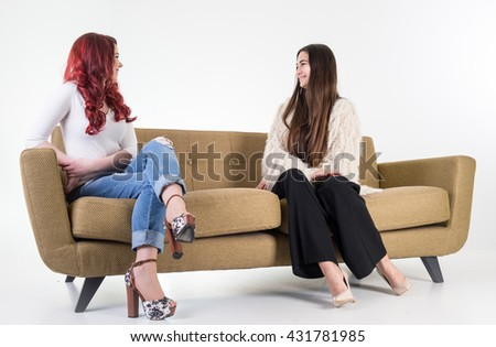 Beautiful attractive girl sitting on modern sofa in white room - stock photo