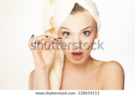 beautiful attractive girl with a towel on her head fixes her makeup with a cotton swab
