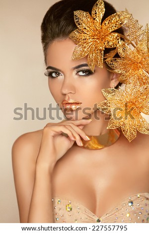 Beautiful Attractive Girl With Golden Flowers. Beauty Model Woman Face. Perfect Skin. Professional Make-up. Makeup. - stock photo