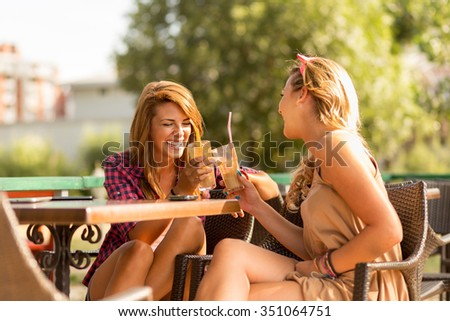Beautiful attractive girls sitting in an outdoor cafe, having an interesting conversation and drinking coffee - stock photo