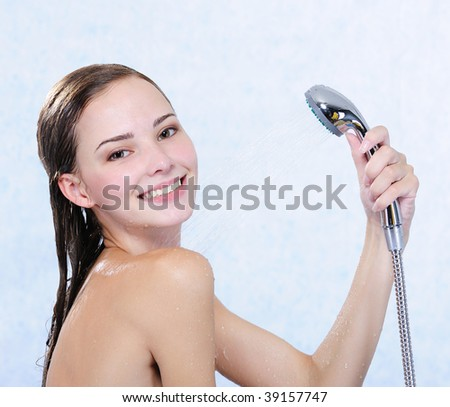 Beautiful attractive happy naked girl taking shower - stock photo