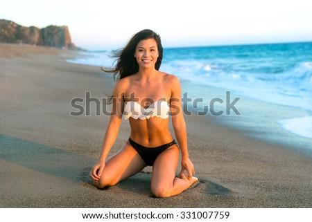 Beautiful attractive happy smile woman perfect body bikini beach sand ocean tropical model abs athletic single - stock photo