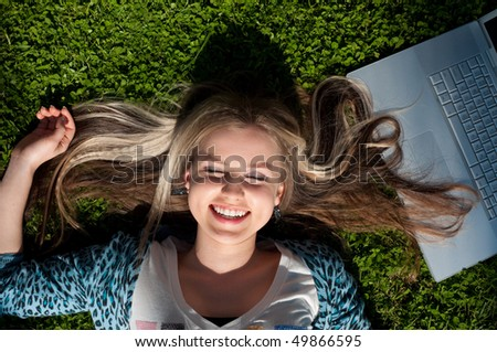 Beautiful attractive lying blond girl with a laptop - stock photo