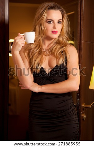 Beautiful attractive sexy and sensuality young adult pretty brunette woman in black elegance dress with a cup of tea at a cafe in door luxury style hotel apartment - stock photo
