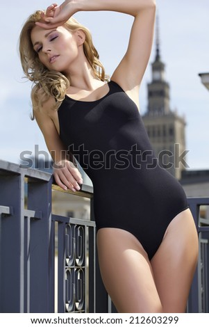 Beautiful attractive slim sexy young adult blonde woman in balcony - stock photo