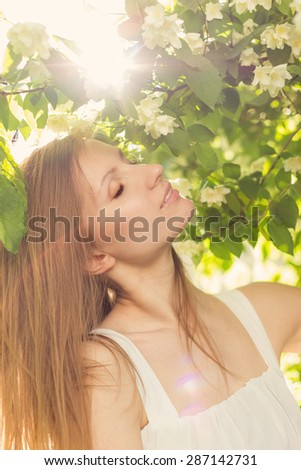 beautiful attractive tender sexy girl in a white dress standing near jasmine and smell the flowers at sunset in the haze of sunlight , the rays of the sun streaming through the leaves - stock photo
