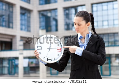 beautiful attractive woman holding a clock and pointing a time for credit - stock photo