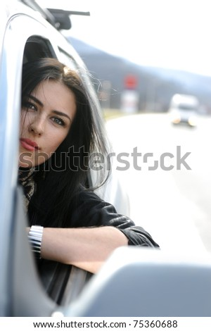 Beautiful attractive woman in car driving on road, looking through the window - stock photo