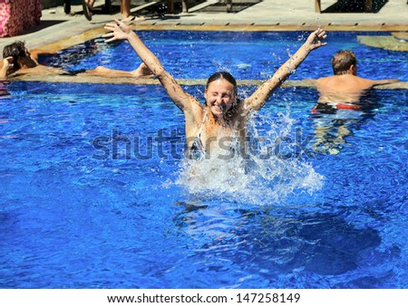 Beautiful attractive woman swimming in the pool, doing jumping up - stock photo