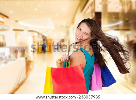 Beautiful attractive young brunette woman carrying shopping bags - stock photo