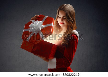 beautiful, attractive, young girl in a red suit Snow Maiden, smiles holding a gift, opens a gift; on a black background, portrait.