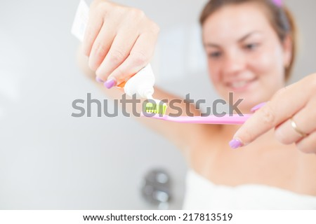 Beautiful/attractive young woman/girl cleaning her teeth/dental hygiene in bathroom (focused on toothbrush) - stock photo