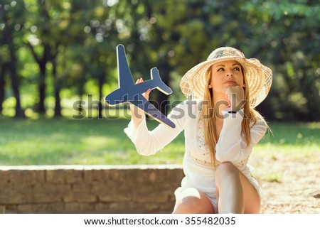 Beautiful attractive young woman having fun, daydreaming and enjoying in the park on a sunny summer day - stock photo
