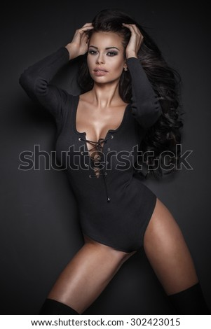Beautiful attractive young woman posing in studio, wearing sexy black clothes. Girl with long black hair and perfect slim body. Looking at camera.  - stock photo