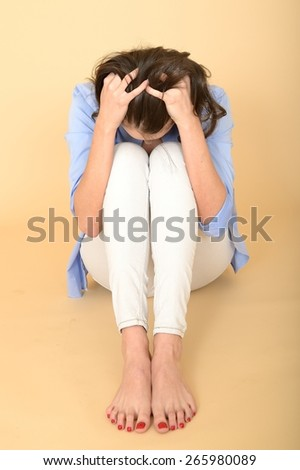 Beautiful Attractive Young Woman Sitting on the Floor Wearing a Blue Shirt and White Jeans Holding Her Head in Shame and Anger - stock photo