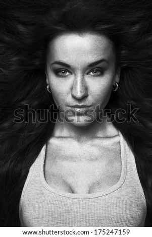 Beautiful attractive young woman with long hair and open neckline on dark background. - stock photo