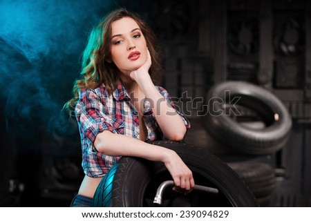 Beautiful auto mechanic. Beautiful young woman leaning at the car tire and looking at camera while sitting in auto repair shop - stock photo
