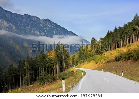 Beautiful autumn day in the Austrian Alps. Road in the mountains of beginners yellowing pines and spruces
