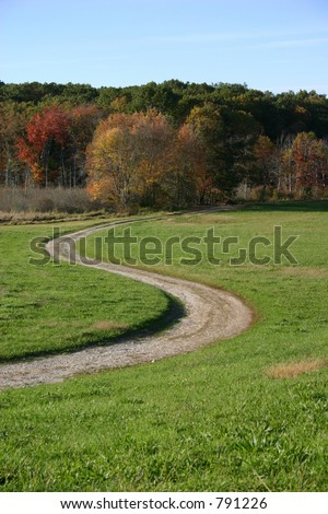 beautiful Autumn day with colorful trees and winding dirt road.