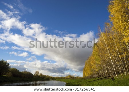Beautiful autumn day with yellow trees and blue sky with clouds. - stock photo