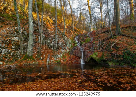 Beautiful autumn foliage, waterfalls and reflection patterns in mountain stream in the forest