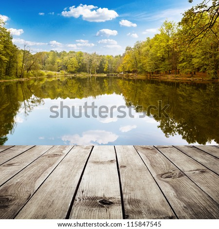 Beautiful autumn forest with reflection in the water and wood planks. Beauty nature background - stock photo