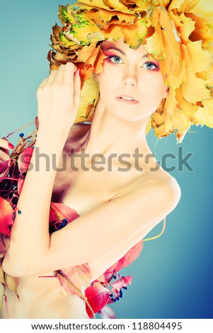Beautiful autumn girl in a hat of maple leaves.