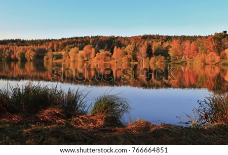 Beautiful autumn landscape at the pond. Colorful trees with blurred, out of focus reflection in the water.