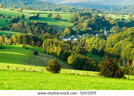 beautiful autumn landscape with little village surrounded by trees - stock photo