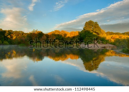 Beautiful autumn landscape with yellow trees reflection in water - stock photo