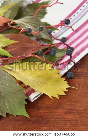 Beautiful autumn leaves with berries on napkin on wooden background