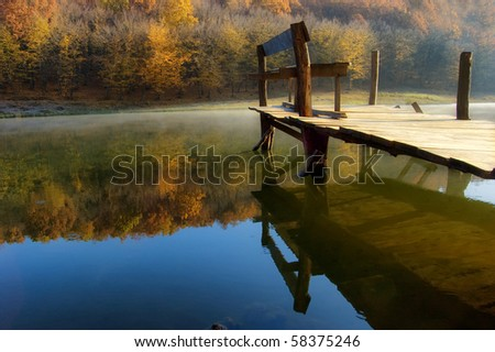 beautiful autumn morning at the lake near a colorful orange forest - stock photo