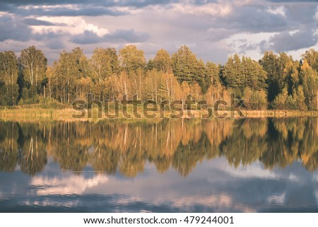 Beautiful autumn sunset at the lake with blue sky, red and orange clouds, green trees and water with reflection - vintage film look
