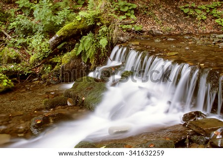 Beautiful autumn waterfall in forest with green foliage