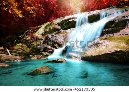 Beautiful autumn waterfall inside forest with warm light - stock photo
