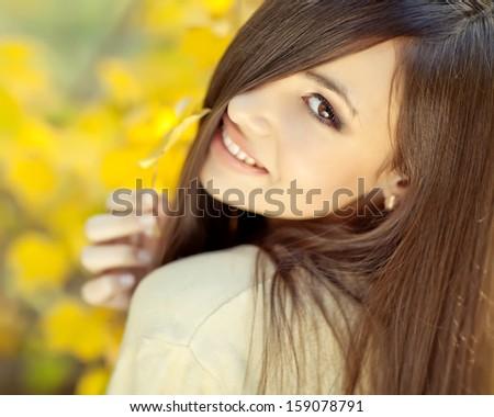 Beautiful autumn woman in golden park - stock photo