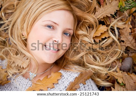 Beautiful autumn woman lying on the floor smiling outdoors - stock photo