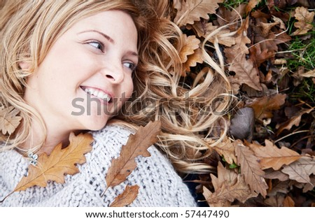 Beautiful autumn woman lying on the floor with leaves around her head - stock photo
