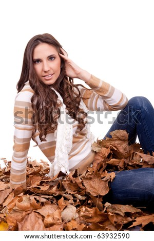 beautiful autumn woman sitting in a pile of dry leaves