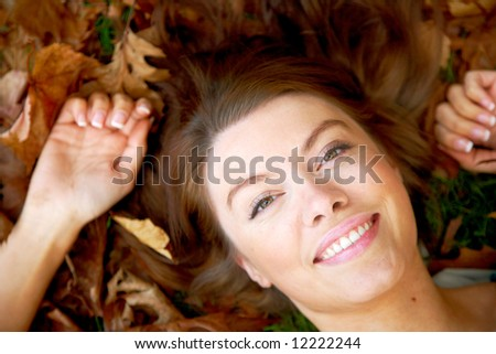 beautiful autumn woman smiling on the floor surrounded by leaves - stock photo